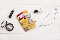 Carteira, cosméticos e acessórios da mulher no fundo cinzento fotos de stock