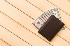 Carteira de couro com dólares no fundo de madeira da tabela Imagens de Stock Royalty Free