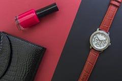A carteira de couro envernizada das mulheres negras, o relógio de pulso das mulheres e verniz para as unhas vermelho em fundos pr foto de stock