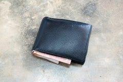 Carteira de couro perdida com dinheiro no assoalho Close-up da carteira que encontra-se no fundo concreto Imagem de Stock Royalty Free