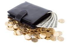 Carteira de couro preta com dólares e as moedas douradas no branco Fotos de Stock Royalty Free