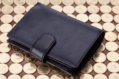 Carteira de couro preta em moedas douradas Fotografia de Stock Royalty Free