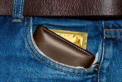 Carteira em um bolso da calças de ganga com um preservativo do ouro fotografia de stock