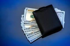 Carteira preta com dólares em um fundo azul imagem de stock