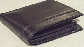 Carteira preta de couro em um close-up claro do fundo Fotos de Stock