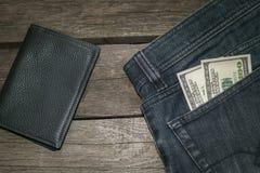 Carteira preta e dólares americanos no bolso das calças de brim Fotografia de Stock Royalty Free