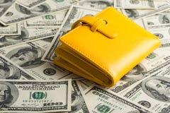 Carteira que descansa em cima de muito Estados Unidos cem dólares Imagens de Stock