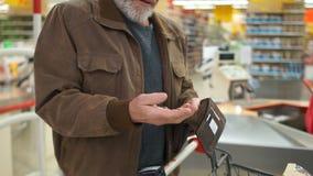 Carteira vazia nas mãos de um homem idoso Pobreza no conceito da aposentadoria Moedas na mão de um pensionista filme