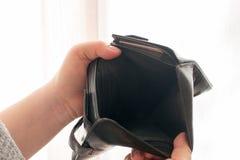 Carteira vazia nas mãos de uma moça, o tema da pobreza imagens de stock royalty free