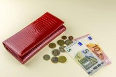 Carteira vermelha da mulher Cédulas dez e cinco euro Algumas moedas Fundo bege fotos de stock