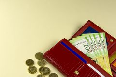 Carteira vermelha da mulher Cédulas em dois cem rublos de russo Algumas moedas Fundo bege Rússia fotografia de stock royalty free