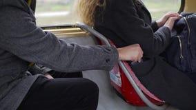 Carteirista que rouba o telefone de um bolso do ` s da mulher no bonde ou no ônibus video estoque
