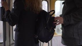 Carteirista que rouba o telefone de uma bolsa do ` s da mulher no bonde ou no ônibus video estoque
