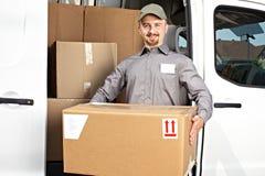 Carteiro com o pacote perto do caminhão de entrega foto de stock