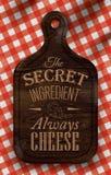 Cartel con el pan que corta al tablero de madera marrón que pone letras al queso del ingrediente secreto siempre. Imágenes de archivo libres de regalías