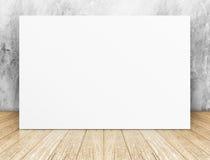 Cartel cuadrado en blanco blanco en muro de cemento y sitio de madera del piso foto de archivo libre de regalías