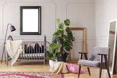 Cartel de la maqueta en interior gris del sitio del bebé con las plantas verdes y la butaca retra, fotografía de archivo
