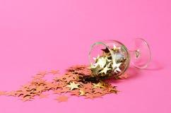 Cartel del partido del Año Nuevo con vida inmóvil de la copa volcada con las estrellas decorativas en un fondo rosado minimalisti Imagen de archivo