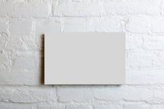 Cartel en blanco blanco en una pared de ladrillo blanca Mofa de la plantilla para arriba para su contenido fotografía de archivo libre de regalías