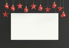 Cartel en blanco con el colgante de bolas y de los ornamentos rojos de las estrellas en fondo concreto oscuro Por Año Nuevo o tem Imagen de archivo libre de regalías