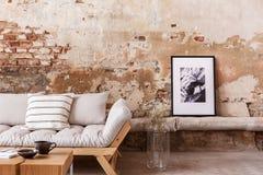 Cartel y flores al lado del sofá de madera gris con las almohadas en completamente interior con la pared de ladrillo fotos de archivo