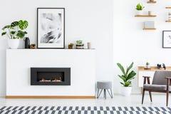 Cartel y planta en la pared blanca con la chimenea en roo vivo acogedor imagen de archivo