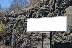 Cartelera blanca en blanco en la calle de la ciudad En la calle y las rocas del fondo Mofa para arriba Cartel en la calle al lado Fotografía de archivo