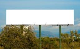 Cartelera blanca enorme con el cielo y la montaña Imagenes de archivo