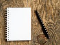 Cartelera con la hoja en blanco para las notas y el lápiz en fondo de madera en blanco abstracto Foto de archivo libre de regalías