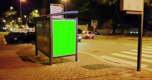 Cartelera con una pantalla del verde de la llave de la croma en una calle de la noche de la ciudad de los coches del tráfico, noc