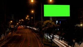 Cartelera de publicidad en blanco al lado del camino con tráfico en la noche metrajes