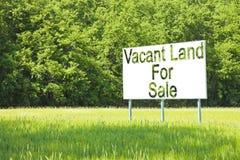 Cartelera de publicidad sumergida en una escena rural con la tierra vacante en venta escrita en ella - imagen con el espacio de l fotografía de archivo