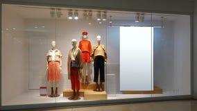 Cartelera en blanco de los maniquíes femeninos de la ventana de la tienda de la ropa fotografía de archivo