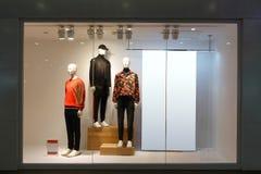 Cartelera en blanco de los maniquíes masculinos de la ventana de la tienda de la ropa imagenes de archivo