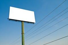 Cartelera en blanco del anuncio con el cielo azul y los cables Fotografía de archivo libre de regalías