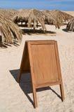 Cartelera en blanco en la playa de la arena foto de archivo