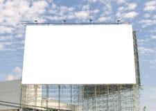 Cartelera en blanco grande en el camino con el fondo de la opinión de la ciudad Foto de archivo libre de regalías