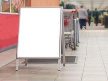 Cartelera en blanco en un supermercado, al lado de los carros de la compra imagen de archivo