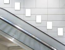 Cartelera en blanco vertical con el fondo de la escalera móvil Imagenes de archivo