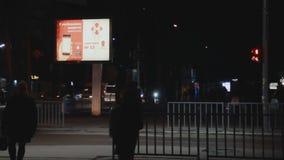 Cartelera iluminada Publicidad del servicio postal popular Nova Poshta Calle de la tarde crosswalk La gente cruza el camino Traff almacen de video