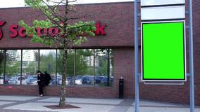 Cartelera verde para su anuncio al lado de Scotiabank almacen de metraje de vídeo