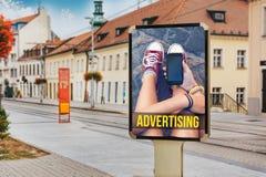 Carteleras con la publicidad de un adolescente con el teléfono móvil En Foto de archivo libre de regalías