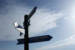Carteles que indican varias direcciones en un lugar turístico de Alicante, en España con un fondo del cielo azul foto de archivo