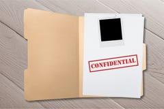 Cartella con le carte confidenziali sulla tavola di legno Immagine Stock