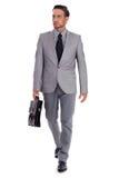 Cartella di trasporto e camminare dell'uomo d'affari Fotografie Stock