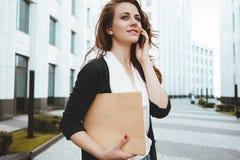 Cartella documenti disponibila e sicurezze fra spazio urbano e conversazione della giovane tenuta della donna di affari sullo sma Fotografie Stock Libere da Diritti
