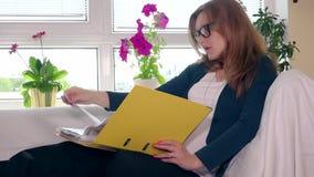 Cartella frustrata del pollice della donna incinta con le carte che si siedono sul sofà a casa archivi video