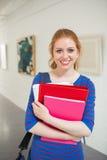 Cartelle sorridenti della tenuta dello studente nel corridoio che esamina macchina fotografica Fotografia Stock