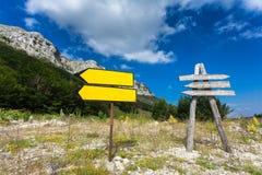 Cartelli sulla strada trasversale alla montagna ed alla foresta Immagine Stock