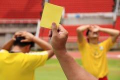 Cartellino giallo della scarpa dell'arbitro di calcio Fotografia Stock